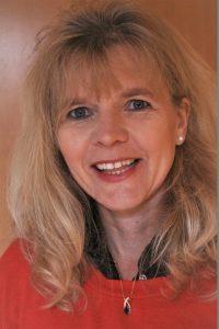 Eine Frau mit blondem Haar, Anfang vierzig, lächelnd