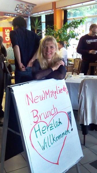 Eine blonde Frau, Anfang 40, lehnt freudig über einem Aufsteller mit der Aufschrift: Neumitglieder-Brunch Herzlich Willkommen!