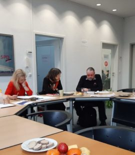 zu sehen sind Mitglieder von Selbst Aktiv und Katja Pähle an einem Tisch im Gespräch. Teller mit Obst und Keksen stehen verteilt auf dem Tisch.