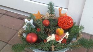 """weihnachtliches Gesteck aus Tanne mit ruten Kugeln, Sternen, Äpfeln, Rehlein, Tannenzapfen, Pferd und dem Schriftzug: """"Frohe Weihnachten"""""""